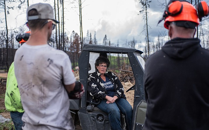"In the months after the Roosevelt Fire roared through Sublette County last September, Andrea ""Andie"" Sramek of Hoback Ranches has organized multiple countywide cleanups to help cut down trees and sift through rubble from the fire, which destroyed 55 homes. (Photo by Dustin Patar/News21)"