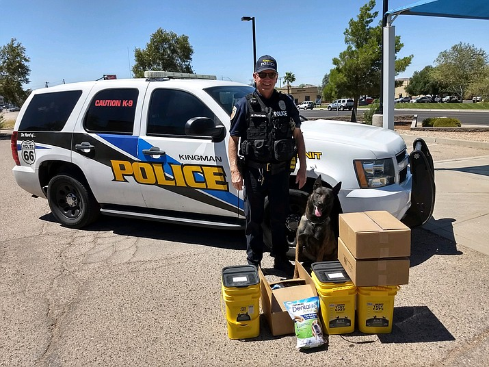 Kingman Police Department Officer Bill Fancher and his K9 partner Sevende stand by their patrol unit with the treats and dental-chew bones donated by For the Luv Of Paws, the no-kill animal sanctuary and shelter in Golden Valley. (Photo by Butch Meriwether/For the Miner)