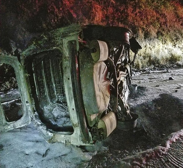 A Humboldt County Sheriff's Department patrol car after it was struck by a falling bear and then hit an embankment, rolled onto its side and burst into flames, near Hoopa, Calif. The deputy managed to escape without serious injury. (Rod Mendes/Hoopa Fire Department via AP)