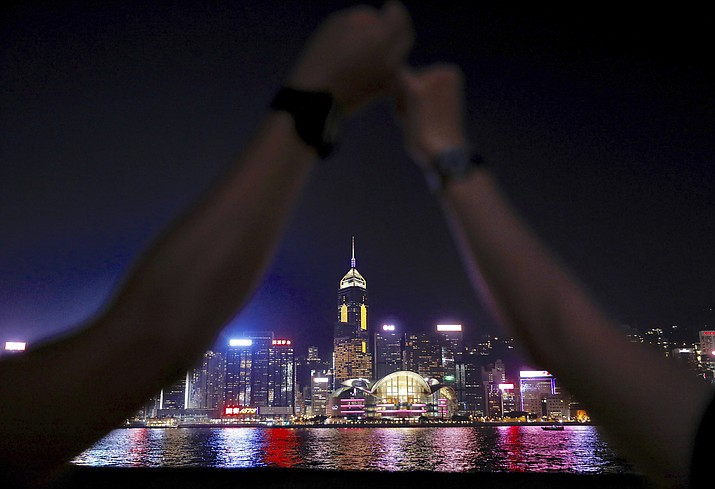 Demonstrators link hands as they gather at the Tsim Sha Tsui waterfront in Hong Kong, Friday, Aug. 23, 2019. Supporters of Hong Kong's pro-democracy movement are linking hands across the semi-autonomous Chinese territory, inspired by a historic protest 30 years ago in the Baltic states when nearly 2 million people formed a human chain to protest Soviet control. (AP Photo/Vincent Yu)