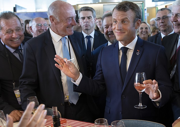 French President Emmanuel Macron, right right, flanked by President of the Nouvelle-Aquitaine region Alain Rousset, center, samples local produce and wine, as he tours the exhibition hall above the international press center on the opening day of the G7 summit, in Anglet, southwestern France, Saturday Aug.24, 2019.  (Ian Langsdon, Pool via AP)