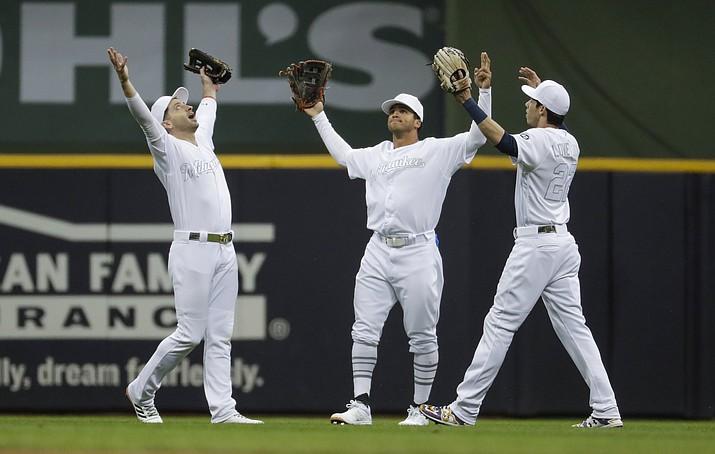 Milwaukee Brewers' Ryan Braun, Trent Grisham and Christian Yelich celebrate after a baseball game against the Arizona Diamondbacks Friday, Aug. 23, 2019, in Milwaukee. The Brewers won 6-1. (Morry Gash/AP)
