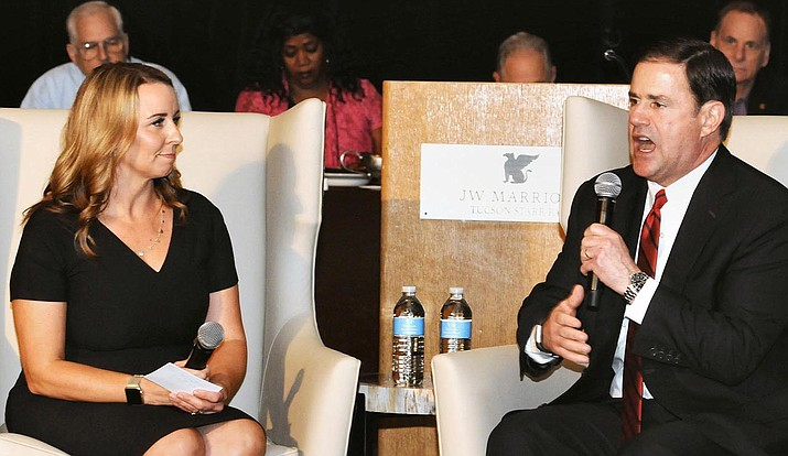 Gov. Doug Ducey chats Thursday with Gilbert Mayor Jenn Daniels at the annual conference of the League of Arizona Cities and Towns in Tucson. The governor later told reporters it is time to revisit a law that restricts the ability of local governments to regulate vacation rentals. Capitol Media Services photo by Howard Fischer