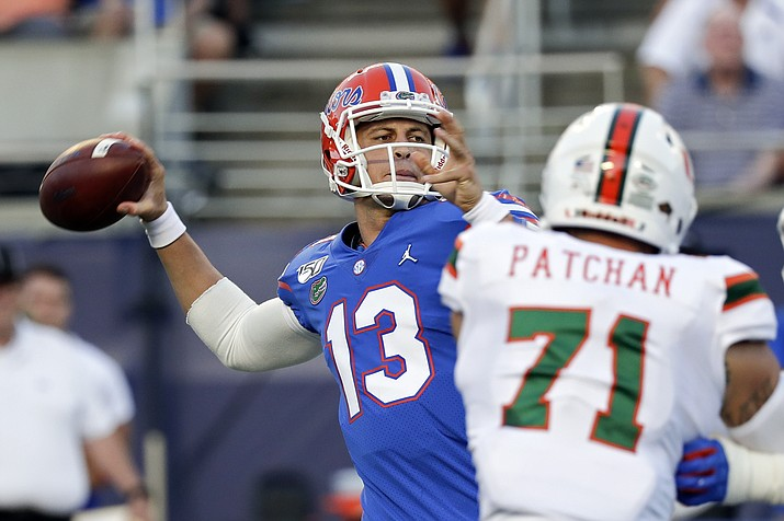 Florida quarterback Feleipe Franks (13) throws a pass as he is pressured by Miami defensive lineman Scott Patchan (71) during the first half of an NCAA game Saturday, Aug. 24, 2019, in Orlando, Fla. (John Raoux/AP)