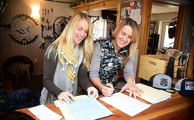 Kate Phelan and Cina McConaughy go through the paperwork they received after paying for the new City of Prescott Business License in January 2017. The City Council is poised to take a look at whether the program should be continued. (Les Stukenberg/Courier, file)