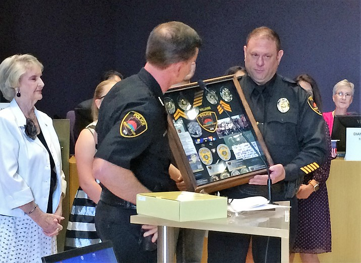 Sgt. Mike Williams, right, accepts a shadow box with 20 years' worth of valuable items from his service with the Prescott Valley Police Department, handed to him by Deputy Police Chief James Edelstein at the Aug. 8 council meeting honoring Williams' service and retirement. (Sue Tone/Tribune)