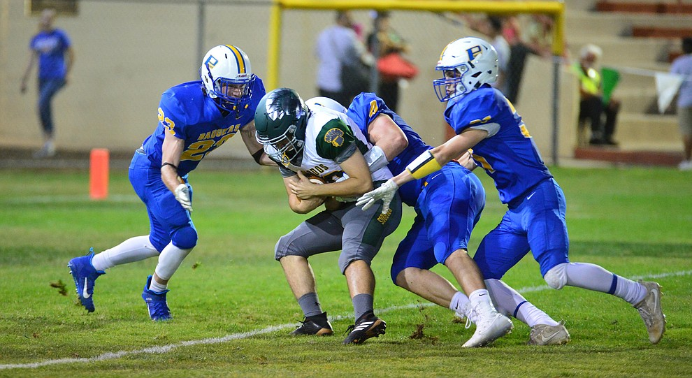 Prescott's sam Giordan (23), Aaron Greene (4) and Nathan Wright (31) tackle the punter for a big loss as the Badgers held their 2019 home opener at Ken Lindley Field Friday, Aug. 30, 2019.  (Les Stukenberg/Courier)