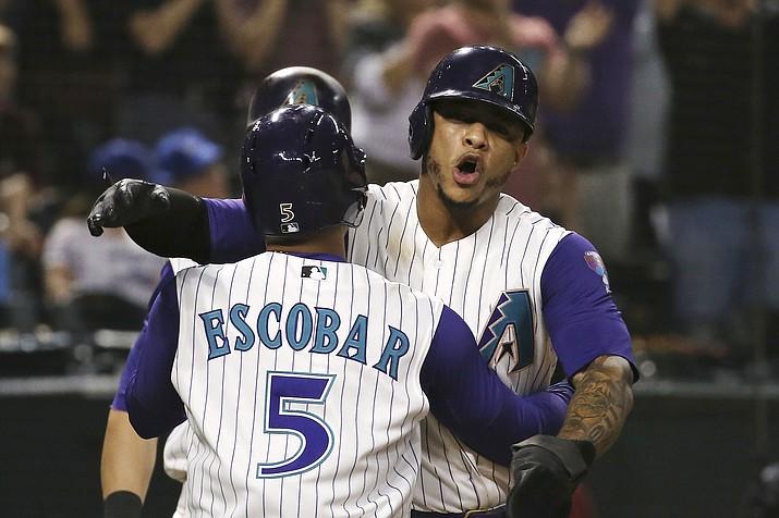 Arizona Diamondbacks' Eduardo Escobar (5) celebrates his three-run home run against the Los Angeles Dodgers with Ketel Marte during the sixth inning of a baseball game Thursday, Aug. 29, 2019, in Phoenix. (Ross D. Franklin/AP, file)
