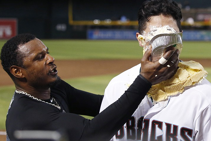 Arizona Diamondbacks' Josh Rojas, right, gets a pie in the face from Adam Jones, left, during an on-field interview after the team's baseball game against the Los Angeles Dodgers on Friday, Aug. 30, 2019, in Phoenix. Rojas had a two-run home run in the seventh as the Diamondbacks won 5-4. (Ross D. Franklin/AP)