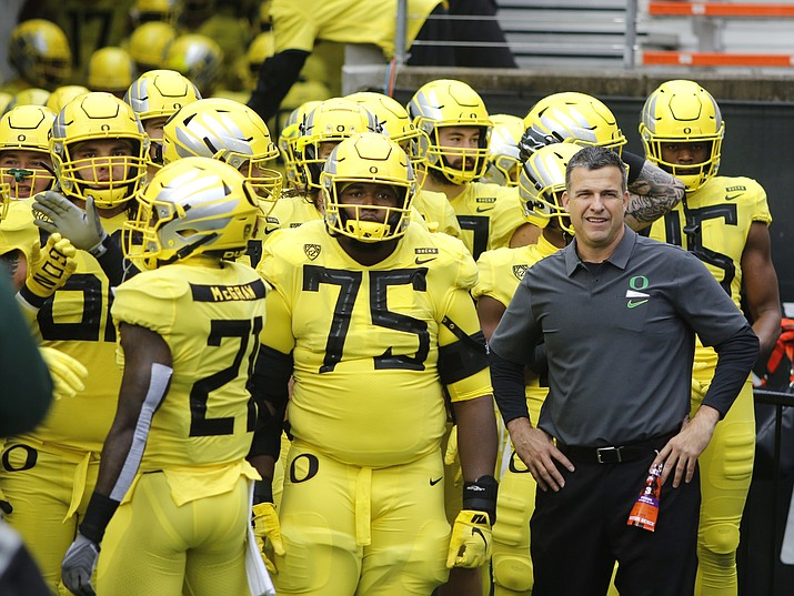 In this Nov. 23, 2018, file photo, Oregon coach Mario Cristobal stands with players before the team's NCAA college football game against Oregon State in Corvallis, Ore. The Ducks are the highest-ranked Pac-12 team and the North Division favorite. They go into Saturday night's game against Auburn, the opener of Cristobal's second season, with a three-game winning streak after a 9-4 season. (Timothy J. Gonzalez/AP, file)