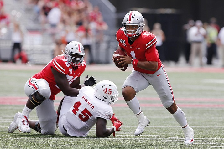 Ohio State quarterback Justin Fields, right, runs up field as teammate Nicholas Petit-Frere, left, blocks Florida Atlantic defensive end Tim Bonner during the second half of an NCAA college football game Saturday, Aug. 31, 2019, in Columbus, Ohio. Ohio State beat Florida Atlantic 45-21. (Jay LaPrete/AP)