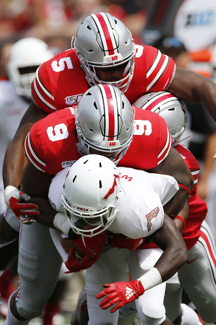 Ohio State defenders Baron Browning, top, and Jashon Cornell, tackle Florida Atlantic receiver Willie Wright during the first half of an NCAA college football game Saturday, Aug. 31, 2019, in Columbus, Ohio. (Jay LaPrete/AP)
