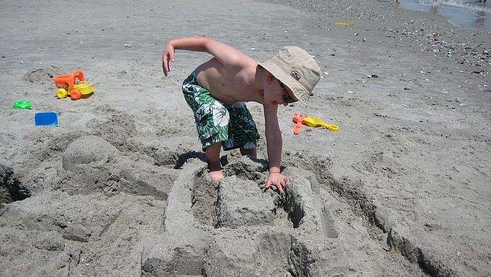 A child builds a sand castle. (Photo by David Beyer, by-sa-cc-2.0, https://bit.ly/2UnRtIQ)