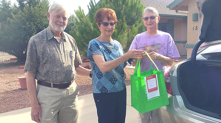 Jim Gibson and Eddie Gibson, neighborhood coordinators, get one of Penny Mathewson's green bags.