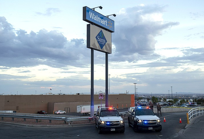 In this Aug. 3, 2019, photo texas state police cars block the access to the Walmart store in the aftermath of a mass shooting in El Paso, Texas. The Bentonville, Arkansas-based discounter says Tuesday, Sept. 3, that it will be discontinuing the sale of short-barrel and handgun ammunition. (AP Photo/Andres Leighton, File)