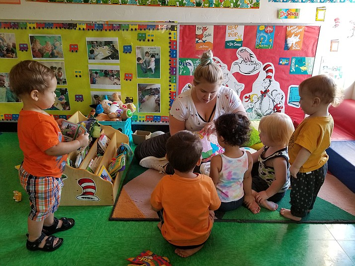 Daycare teacher Meghan Mere reads to 1-year-olds at Learning Castle Children's Center in Prescott Valley on Friday, Aug. 23, 2019. (Max Efrein/Courier)