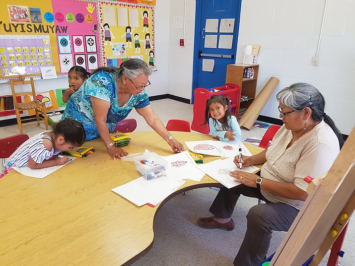 Facilitators help preschool students with school work during a language immersion program. (Photo/Hopi Education Endowment Fund)