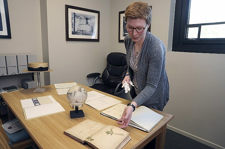 In this Tuesday, Aug. 20, 2019 photo, Lauren Amundson, archivist and librarian, shares the history of some of the oldest artifacts stored at Lowell Observatory in Flagstaff, Ariz. Historians, archivists and librarians in northern Arizona are teaming up to protect artifacts in the event of an internal or external disaster. (Jake Bacon/Arizona Daily Sun via AP)