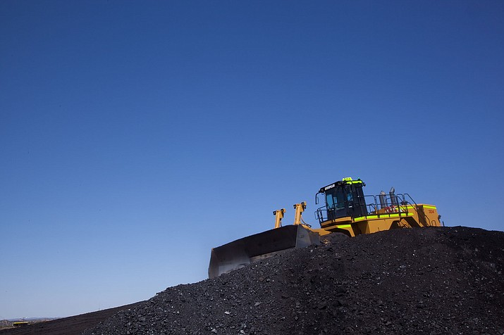 A bulldozer crawls over a pile of coal at Peabody's Kayenta mine on the Navajo Nation in this 2012 photo. The mine is closing this month, ahead of the December closure of its only customer, the Navajo Generating Station. (Photo courtesy Peabody Energy)