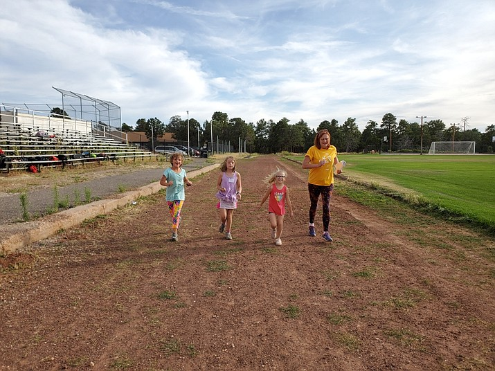 Girls on the Run coach Sandy Angat (far right) keeps young runners moving forward at practice Aug. 22. (Erin Ford/WGCN)