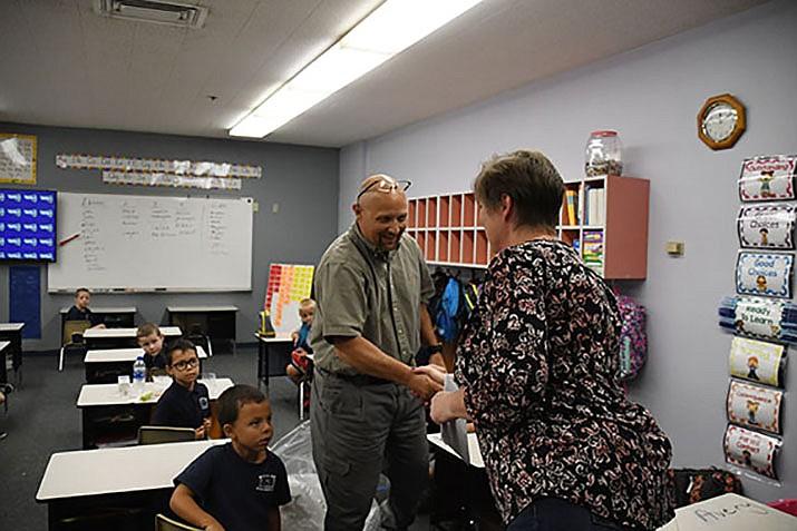 Cerbat teacher Richard Wagner shakes hands with Coleen Hart, American Woodmark Foundation team leader. (Photo by Vanessa Espinoza/Daily Miner)