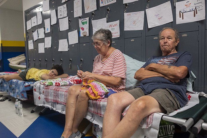 Gordon and Dina Reynolds, with their 11-year-old granddaughter, Abby, sit on cots in the hall way of the North Myrtle Beach High School that is currently being used as a Red Cross evacuation shelter Wednesday, Sept. 4, 2019 in North Myrtle Beach, S.C.  (Jason Lee/The Sun News via AP)