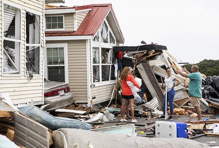 Residents of the Boardwalk RV Park discuss the path of a possible waterspout or tornado, generated by Hurricane Dorian, struck the area, Thursday, Sept. 5, 2019, in Emerald Isle, N.C. (Julia Wall/The News & Observer via AP)