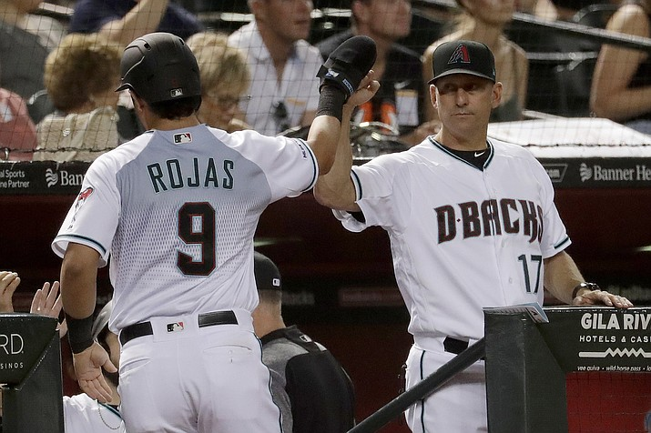Arizona Diamondbacks' Josh Rojas (9) high-fives manager Torey Lovullo after scoring on a base hit by Jake Lamb during a game against the San Diego Padres on Tuesday, Sept. 3, 2019, in Phoenix. (Matt York/AP)