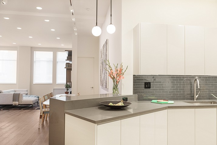 This photo provided by Jennifer Bunsa of Bunsa Studio Interiors shows a kitchen designed by Bunsa in New York. Softly glowing globe lights offer ample light that isn't harsh or overly bright. (Anna White/Bunsa Studio Interiors via AP)