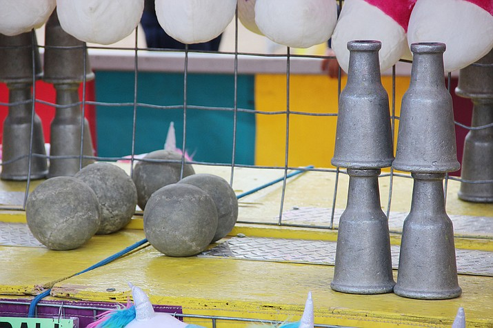 One Shot is one of 10 carnival games offered at the 2019 Yavapai County Fair. The objective is to knock all four metal pins over with the single toss of a softball. (Max Efrein/Courier)