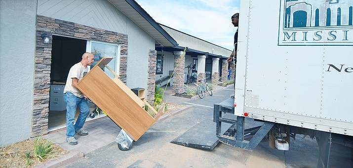 Members of the homeless community, volunteers and staff lift furniture into the Old Town Mission moving truck at the Verde Valley Homeless Coalition day shelter on Friday. VVN/Vyto Starinskas