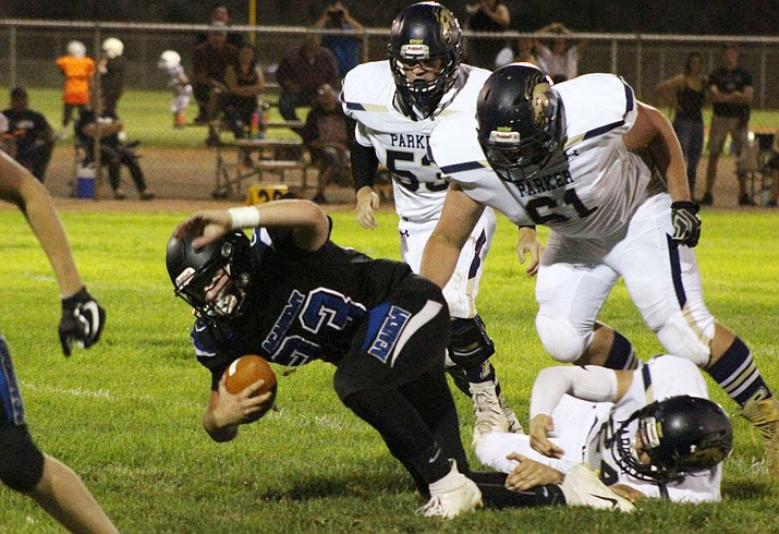 Kingman Academy's Isaac Carter is pulled down by a pack of defenders during a 32-8 loss to Parker Friday night at Southside Park. (Photo by Beau Bearden/Daily Miner)