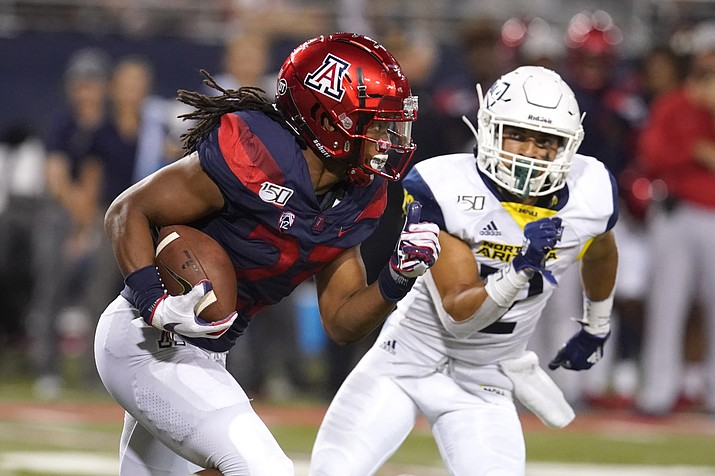 Arizona running back Gary Brightwell (23) runs away from Northern Arizona defensive back Anthony Sweeney in the second half during a game, Saturday, Sept. 7, 2019, in Tucson, Ariz. (Rick Scuteri/AP)
