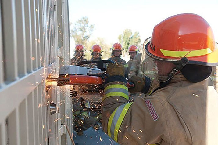 Mohave Community College is now accepting applications for its 2020 Fire Academy. Above, students train to use a rotary saw to gain entry through a metal door during a previous academy.  (Photo courtesy of MCC)