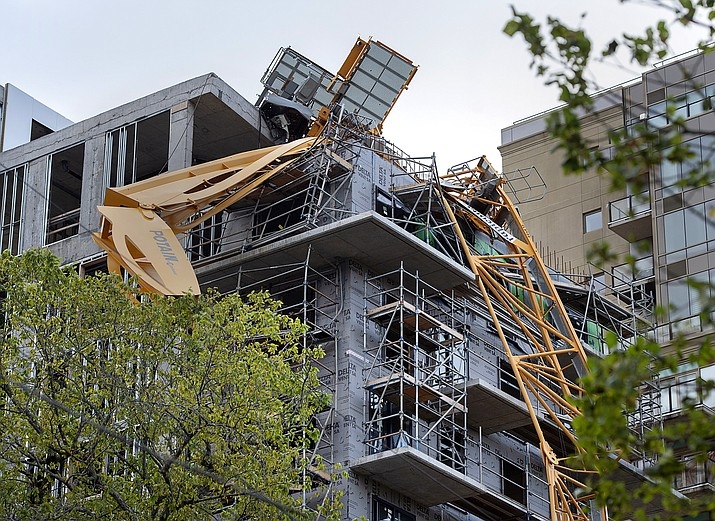 A toppled building crane is draped over a new construction project after Hurricane Dorian swept through the area in Halifax, Nova Scotia, on Sunday, Sept. 8, 2019. Hurricane Dorian brought wind, rain and heavy seas that knocked out power across the region, left damage to buildings and trees as well as disruption to transportation. (Andrew Vaughan/The Canadian Press via AP)