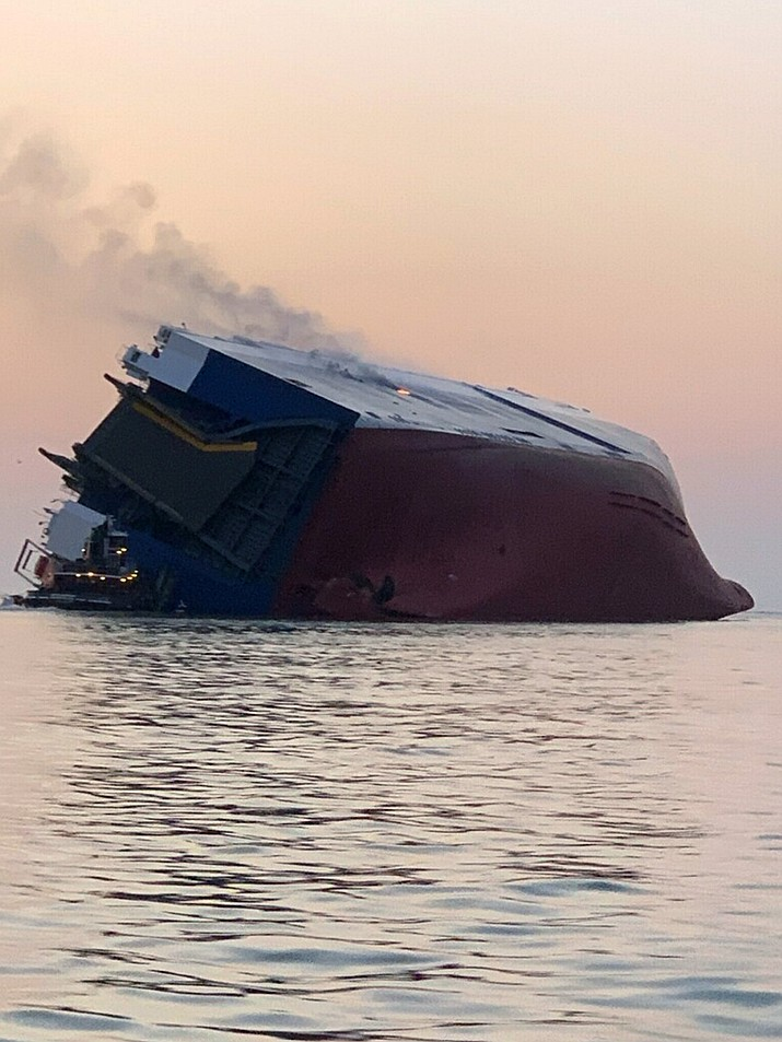 Coast Guard crews and port partners respond to an overturned cargo vessel with a fire on board Sunday, Sept. 8, 2019, in St. Simons Sound, Ga. (U.S. Coast Guard via AP)