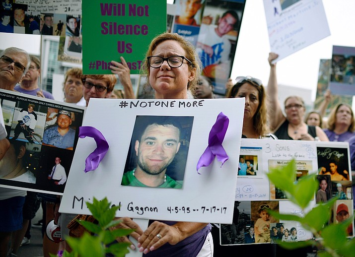 In this Friday, Aug. 17, 2018, file photo, Christine Gagnon of Southington, Conn., protests with other family and friends who have lost loved ones to OxyContin and opioid overdoses at Purdue Pharma LLP headquarters in Stamford, Conn. Gagnon lost her son Michael 13 months earlier. OxyContin maker Purdue Pharma is expected to file for bankruptcy after settlement talks over the nation's deadly overdose crisis hit an impasse, attorneys general involved in the talks said Saturday, Sept. 7, 2019, in a message to their counterparts across the country. (Jessica Hill/AP, file)