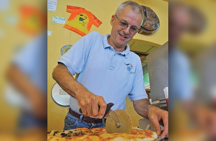 In this undated file photo, Bill Tracy of Bill's Pizza slices up a freshly baked pizza. Tracy died Sept. 5, 2019. (Courier file photo)