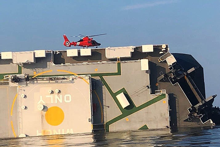 In this image released by the U.S. Coast Guard, a USCG helicopter hovers over an overturned cargo ship in St. Simons Sound, Ga., on Monday, Sept. 9.  (U.S. Coast Guard photo)
