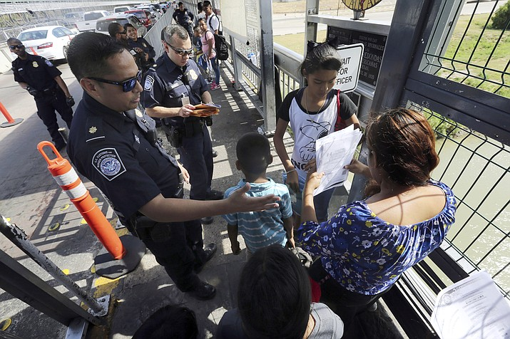 In this July 17, 2019, file photo, a United States Customs and Border Protection Officer checks the documents of migrants before being taken to apply for asylum in the United States, on International Bridge 1 in Nuevo Laredo, Mexico. A federal judge in California has reinstated a nationwide halt on the Trump administration's plan to prevent most migrants from seeking asylum on the U.S.-Mexico border. U.S. District Judge Jon Tigar on Monday, Sept. 9 ruled that an injunction blocking the administration's policy from taking effect should apply nationwide. (Marco Ugarte/AP, file)