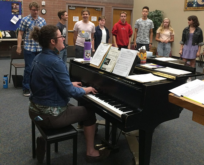 """Choral director Erin Sobo playing the piano as the mixed ensemble choir does vocal exercises and then performs one of their Yavapai Chorale Invitational tunes, """"Loch Lomond."""" (Nanci Hutson/Courier)"""