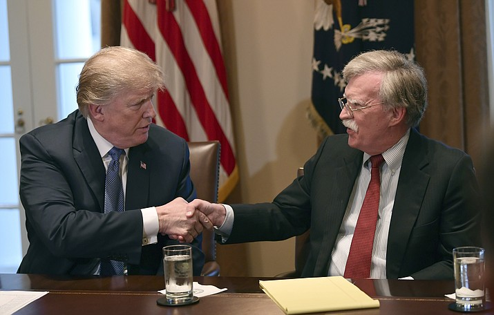 In this April 9, 2018 photo, President Donald Trump, left, shakes hands with national security adviser John Bolton in the Cabinet Room of the White House in Washington at the start of a meeting with military leaders. Trump has fired Bolton. Trump tweeted Tuesday that he told Bolton Monday night that his services were no longer needed at the White House. (Susan Walsh/AP, file)