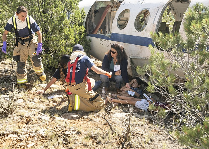 A downed airplane was purchased for $600 from an airplane graveyard for the purpose of a simulated disaster drill Aug. 30 at Grand Canyon Airport in Tusayan. From left: Tusayan firefighters Kate Maragos and Molly Woolley, along with Tusayan employee Veronica Cockrum and local residents Magen Timeche and her children, Trevor, Saavedra and Emma take part in the drill. (Veronica R. Tierney/WGCN)