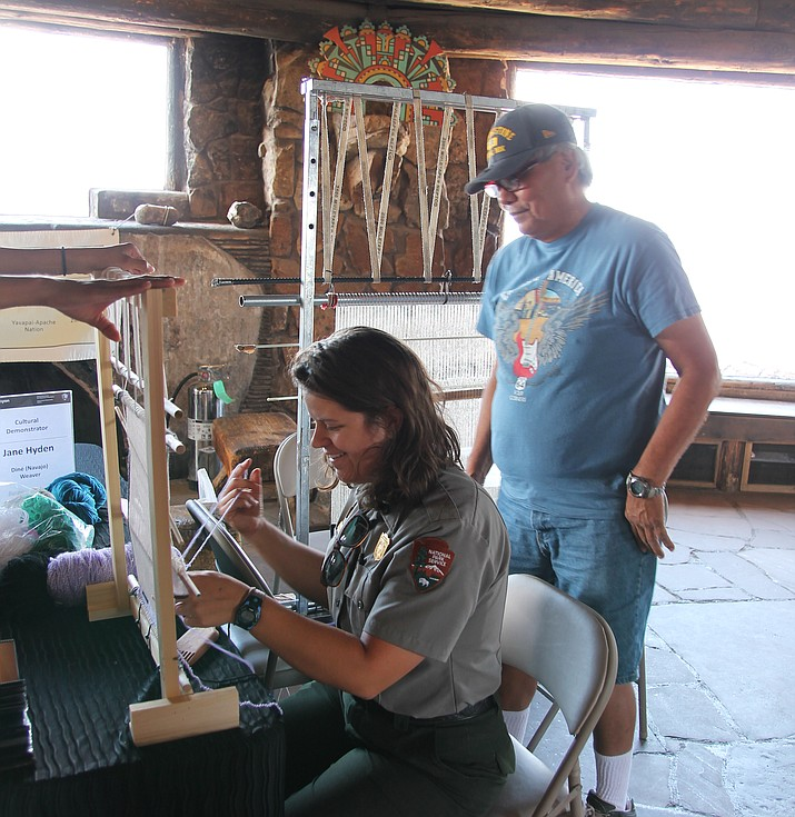 Bill Nez teaches a park ranger how to secure wool threads on a small loom. (Erin Ford/WGCN)