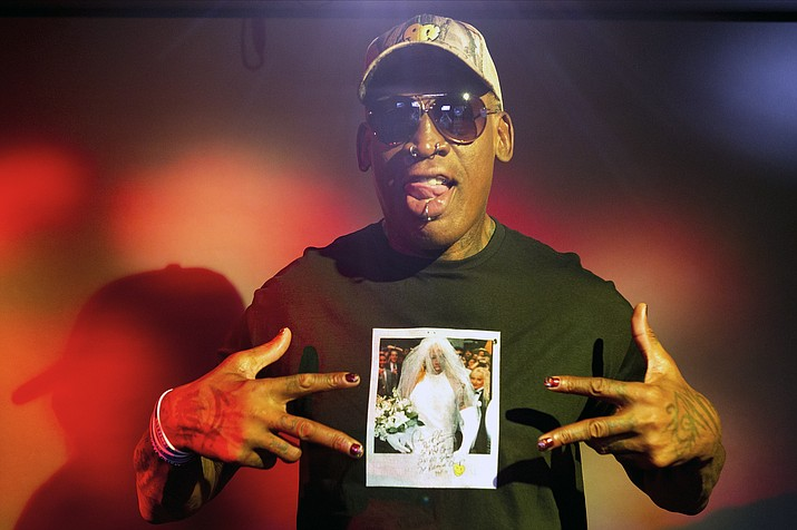 "In this Monday, Sept. 9, 2019, photo, former NBA star Dennis Rodman poses wearing a T-shirt depicting himself in a wedding dress at a 1996 book promo event, in Los Angeles. After a career of spectacular highs and very public lows, Dennis Rodman keeps finding new ways to surprise. The former NBA star, featured in a new ESPN documentary, weighs in on his personal brand, bisexual athletes, North Korea and Trump. Rodman's spectacular personal highs and very public lows are the subject of the new ESPN ""30 For 30"" documentary ""Dennis Rodman: For Better or Worse."" (Damian Dovarganes/AP)"