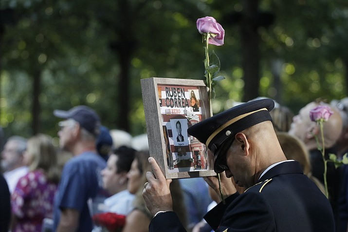 A man holds a photo of a victim during a ceremony marking the 18th anniversary of the attacks of Sept. 11, 2001, at the National September 11 Memorial, Wednesday, Sept. 11, 2019, in New York. (Mark Lennihan/AP)