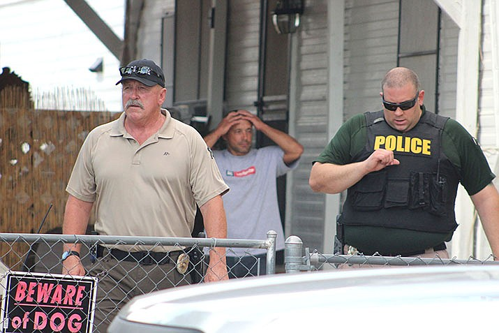 In this July 2018 file photo, Jeremiah Grant Peacey, background, watches authorities leave his property July 17. Peacey has been accused of taking a suitcase containing about $170,000. In June, a Valle Vista woman reported leaving the cash-filled suitcase on the bottom of a shopping cart at Walmart. (Daily Miner file photo)