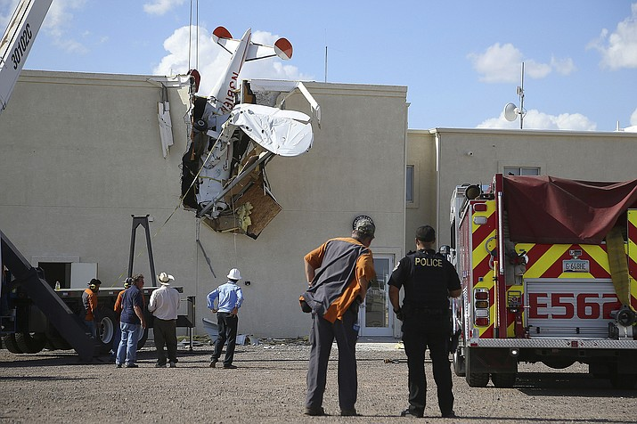Police and fire personnel look on as workers remove a single-engine plane after it crashed into the terminal building shortly after takeoff at the Ak-Chin Regional Airport Tuesday, Sept. 10, in Maricopa, Ariz. The two people onboard suffered non-life-threatening injuries. (AP Photo/Ross D. Franklin)