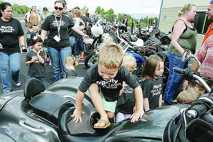 A young Flip City Gym-Preschool student climbs across a large motorcycle during last year's Little Bikers event. The educational event, meant to teach young children about motorcycles and how to watch for them, will involve Thursday, Sept. 19 visits to Flip City and to Cottonwood Community School. VVN/File photo