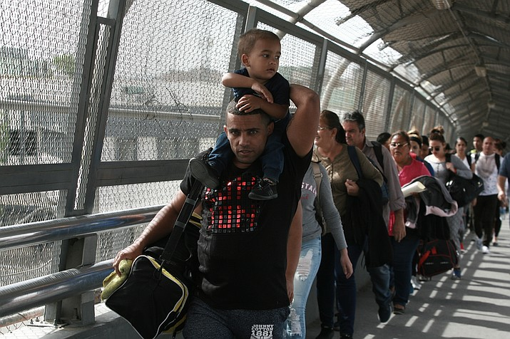 """In this April 29, 2019 file photo, Cuban migrants are escorted by Mexican immigration officials in Ciudad Juarez, Mexico, as they cross the Paso del Norte International bridge to be processed as asylum seekers on the U.S. side of the border. Mexican Foreign Secretary Marcelo Ebrard said Thursday, Sept. 12, 2019 that Mexico's government doesn't agree with an """"astonishing"""" U.S. Supreme Court order that would block migrants from countries other than Mexico and Canada from applying for asylum at U.S. borders. (Christian Torres/AP, file)"""